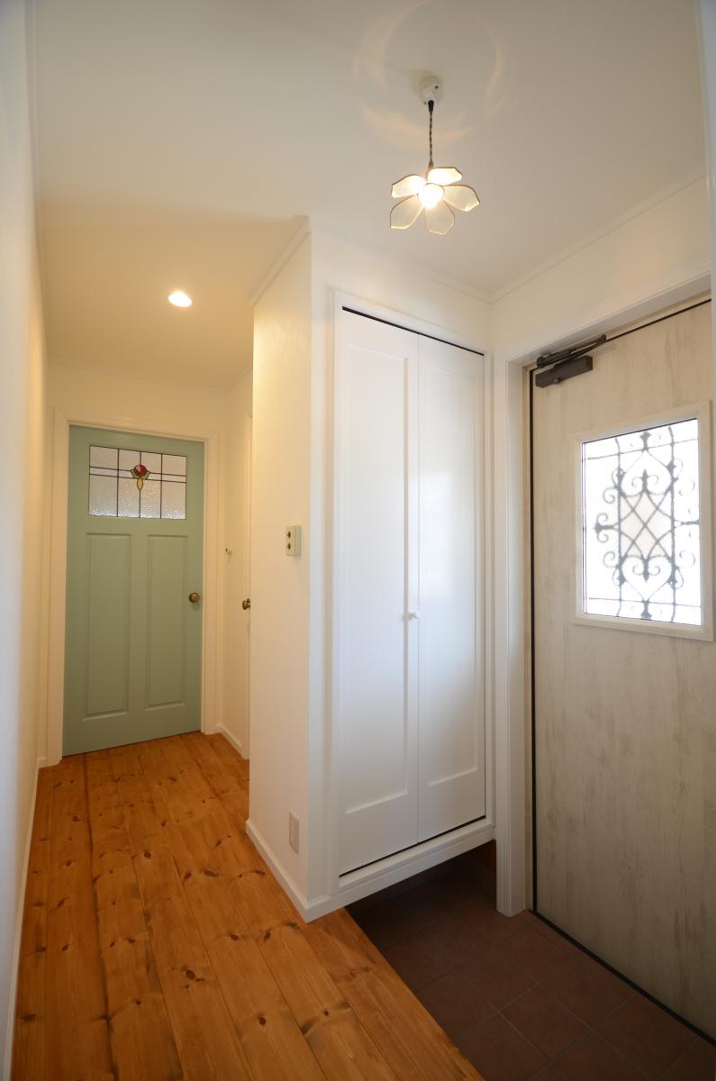 白壁と無垢材がソフトな雰囲気の玄関。靴箱の扉も白で統一、おしゃれな雑貨屋のような雰囲気です。