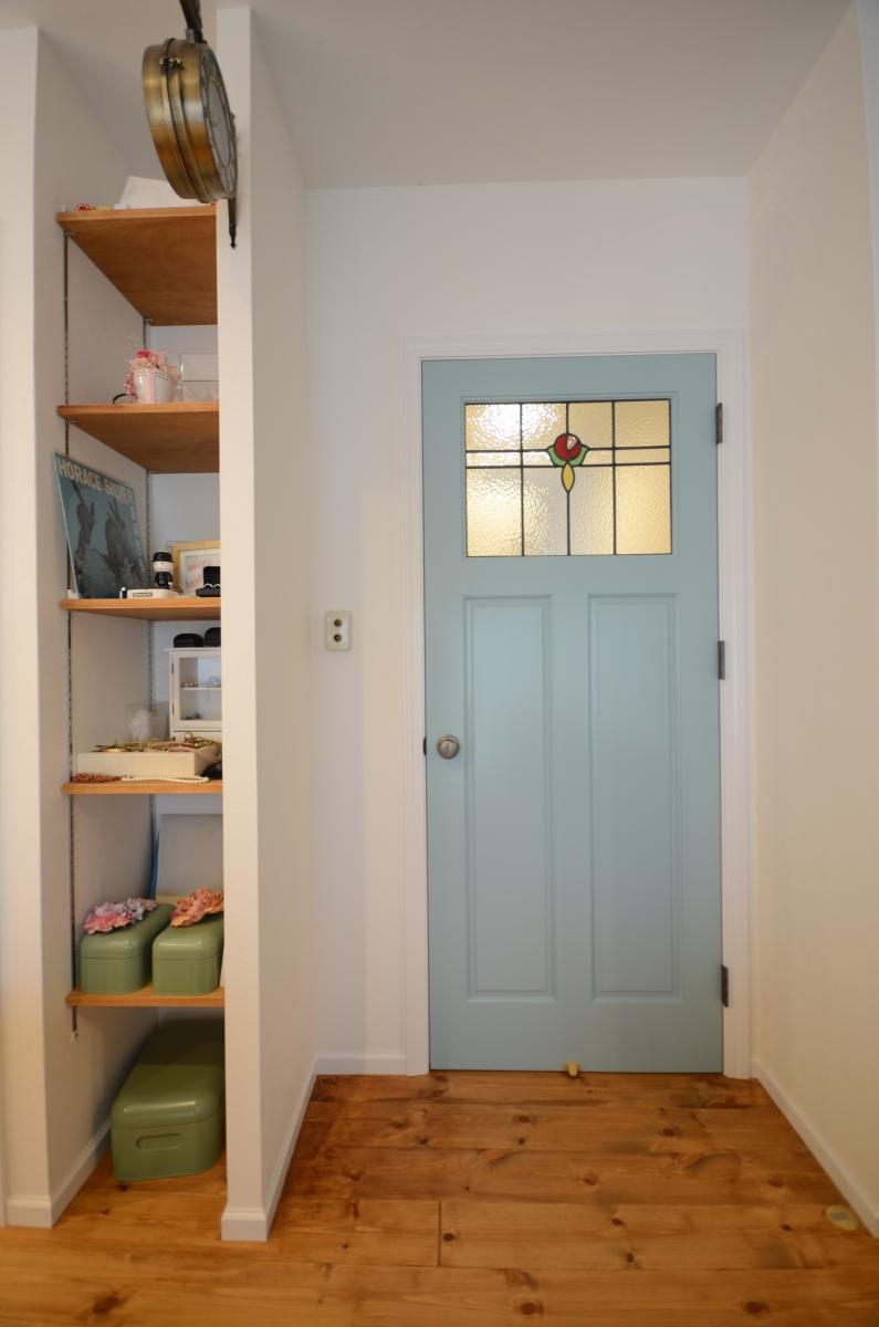 廊下とリビングの間には、ステンドグラスのアレンジがかわいらしい青いドアが存在感を発揮。