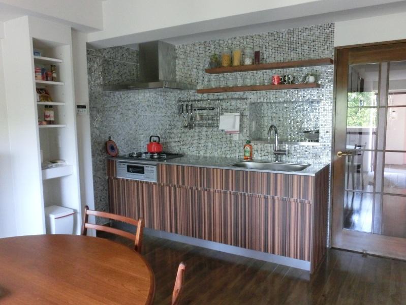 オープンキッチンで広々と使え、壁一面のモザイクタイルも光の加減で見え方も微妙に変わり空間をおしゃれに演出